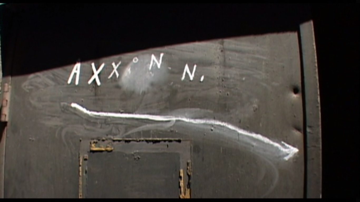 A still from 'Inland Empire'. 'AXXON N.' scrawled in chalk, on a shadowy doorway, with a wobbly chalk arrow pointing off to one side.