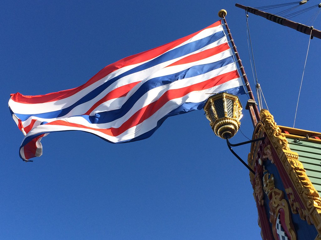 Photograph of a red, white, and blue-striped flag flying from the decorated stern of a ship, against a clear blue sky.