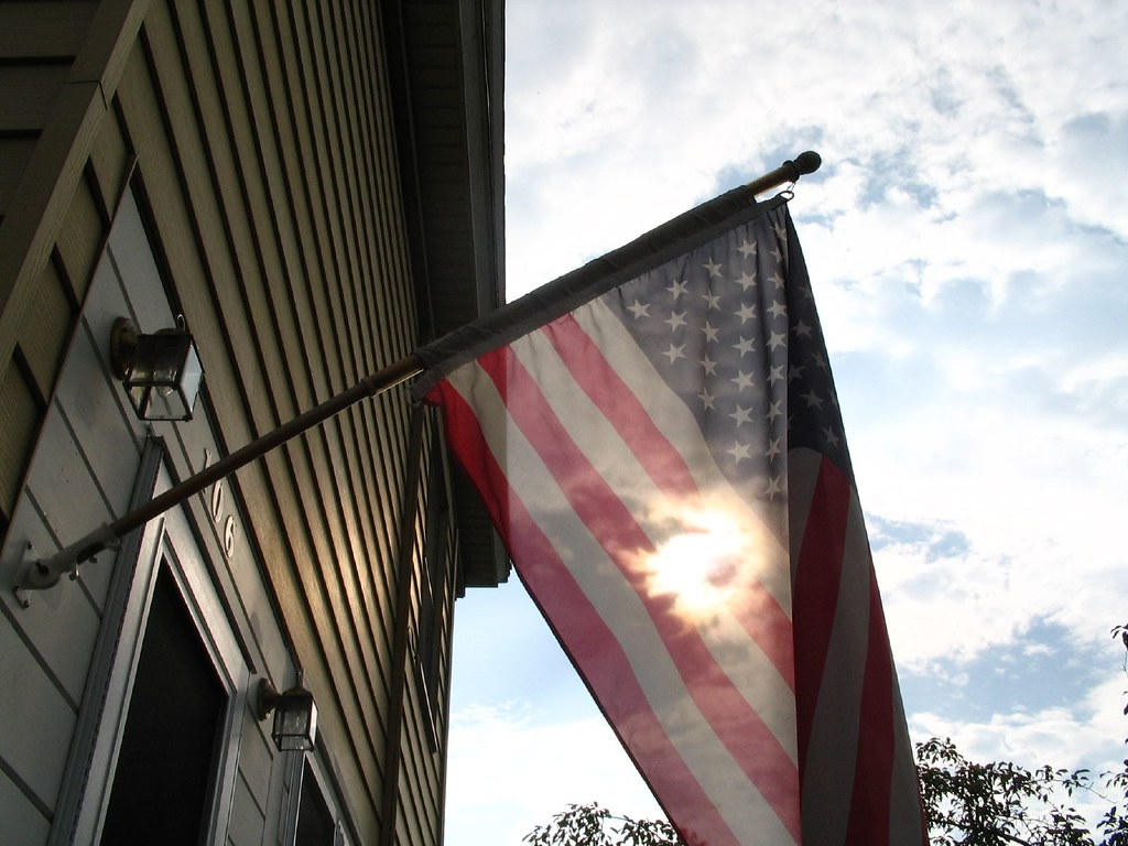 Photograph of an American flag by the door of a home. The flag waves directly between the camera and the sun, which burns like an eerie flame in the middle of the cloth.