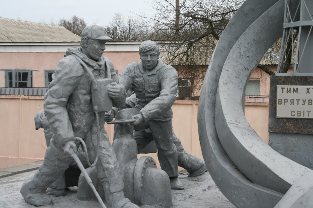 Photograph of a statue at Chernobyl, depicting two grim-faced men in hazmat suits turning valves and operating other equipment.