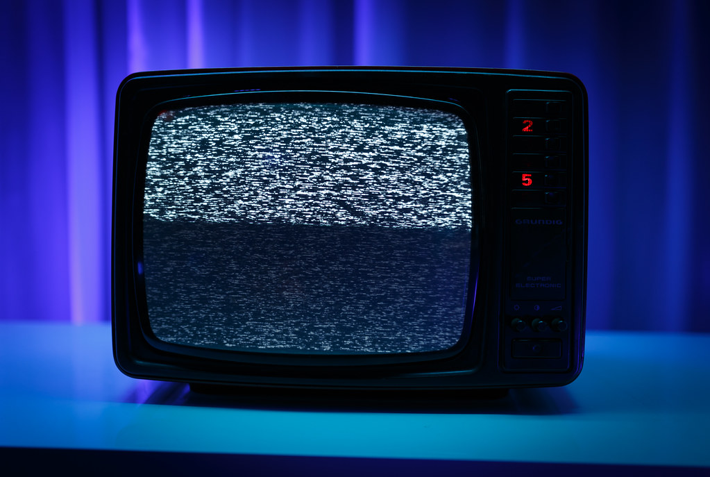 Photograph of an old TV set, tuned to a staticky pattern.