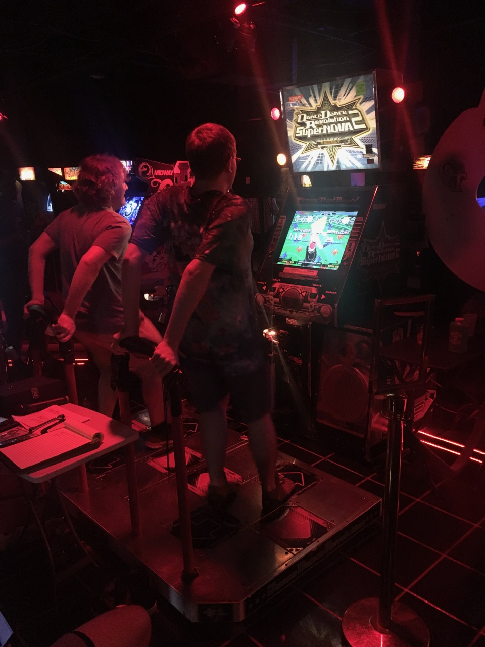 Two young men playing 'Dance Dance Revolution', side-by-side.