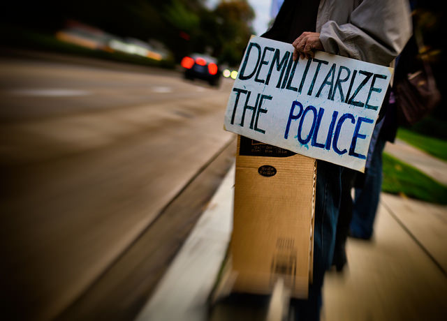 Photograph of a protester holding a sign that  reads 'Demilitarize the police'.