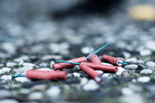 Photograph 'What's Wrong With the Kids These Days?' by André Hofmeister, CC-BY-SA 2.0. (A close-up of a few small, unexploded fireworks sitting on a gravel sidewalk.)