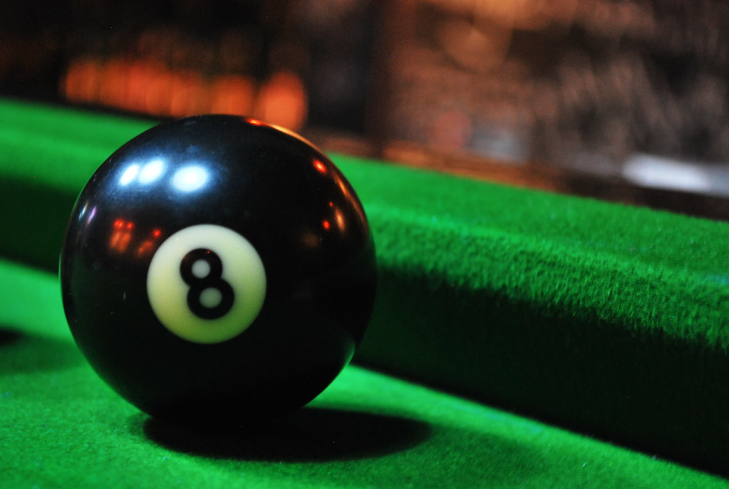A photograph of an 8 ball on a green felt pool table.