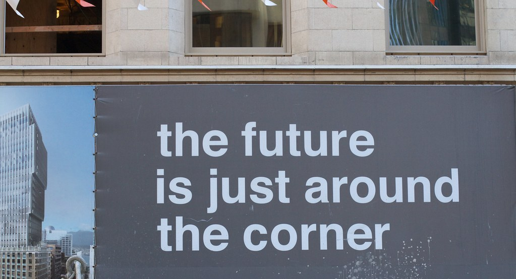 Photograph of a billboard reading 'The future is just around the corner'.