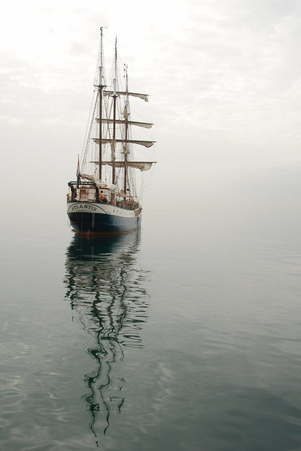 Photograph of a square-rigged sailing ship with 'Atlantis' written on its stern, seeming to fade into a foggy backdrop.