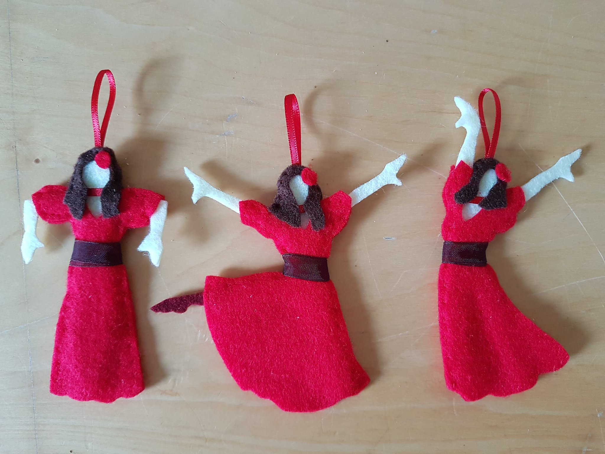 A photograph of three Christmas tree ornaments, each a little felt model of Kate Bush in a dancing pose, dressed as she appears in the video of her song 'Wuthering Heights'.