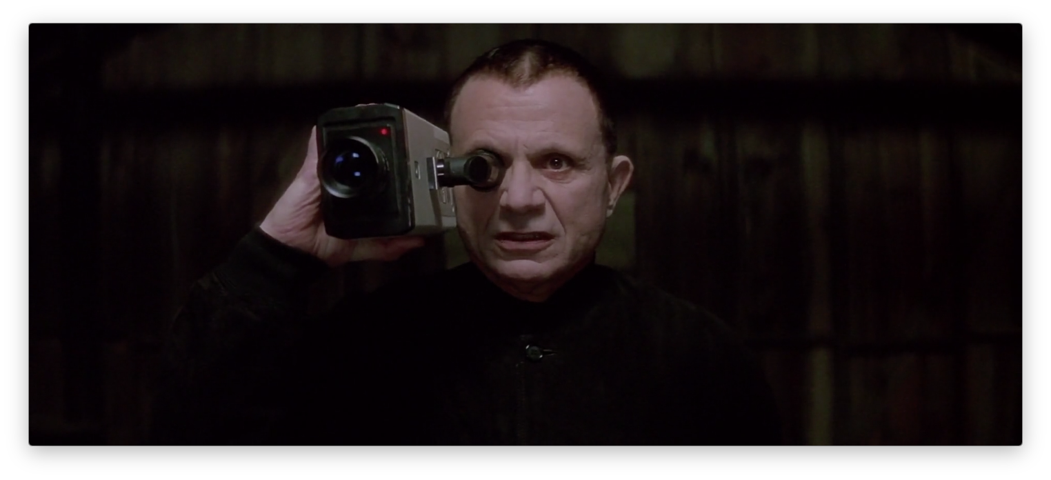 A still from the film 'Lost Highway': A pale man stands against a black background, holding a bulky camcorder up to his eye, and sneering.