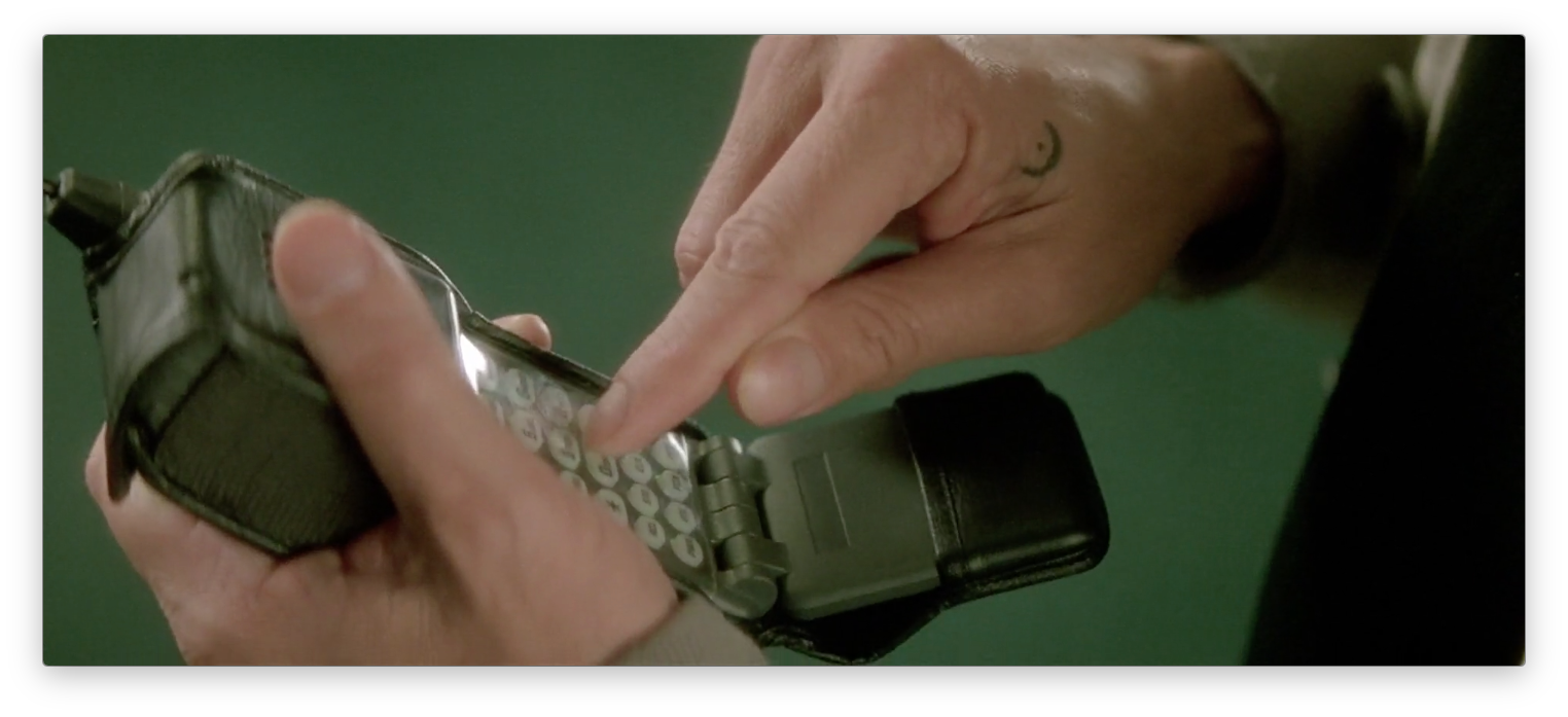 A still from the film 'Lost Highway': A close-up of a man's hands dialing a number on a bulky, 1990s-era cellular phone.