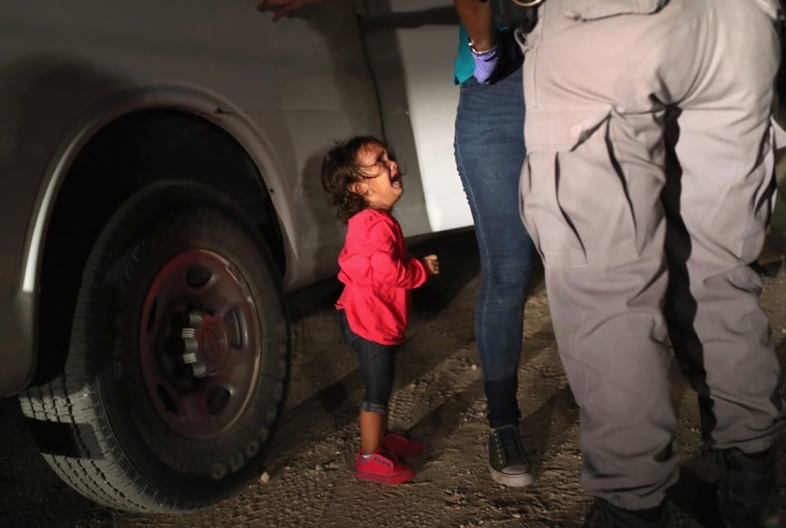 A child looks up and weeps as her mother is patted down by an immigration officer.