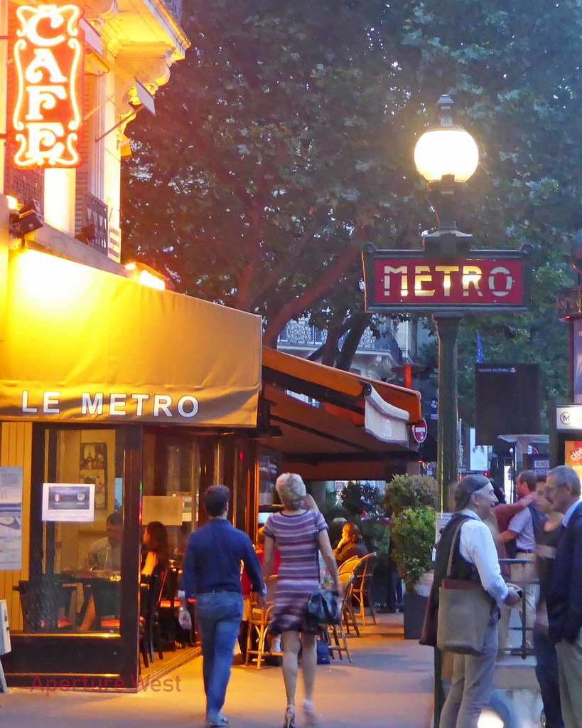 Photograph of people gathered at, and strolling past, a Parisian café at dusk.