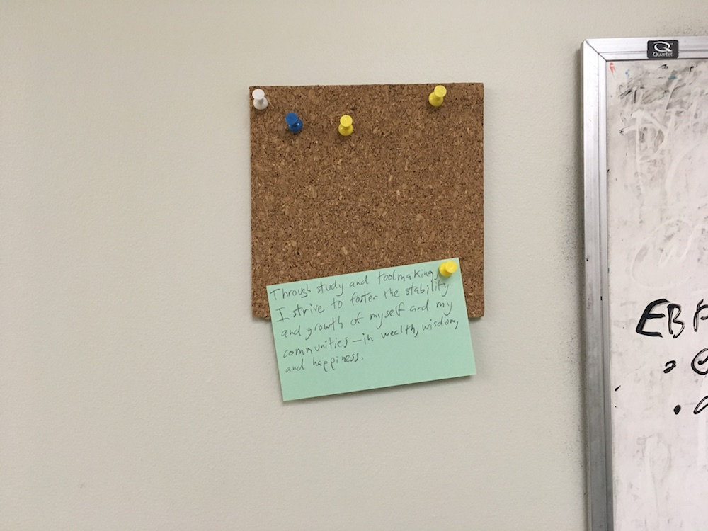 Photograph of an index card pinned to a corkboard. Written on it, in pencil, is the personal mission statement described near the end of this post.