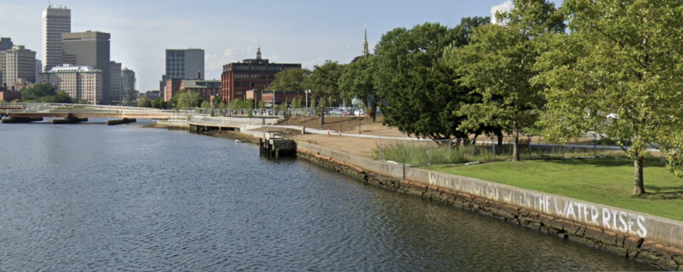 Photograph of the Providence skyline, across a river. Painted on the river's concrete bank are the words: WHERE WILL WE GO WHEN THE WATER RISES
