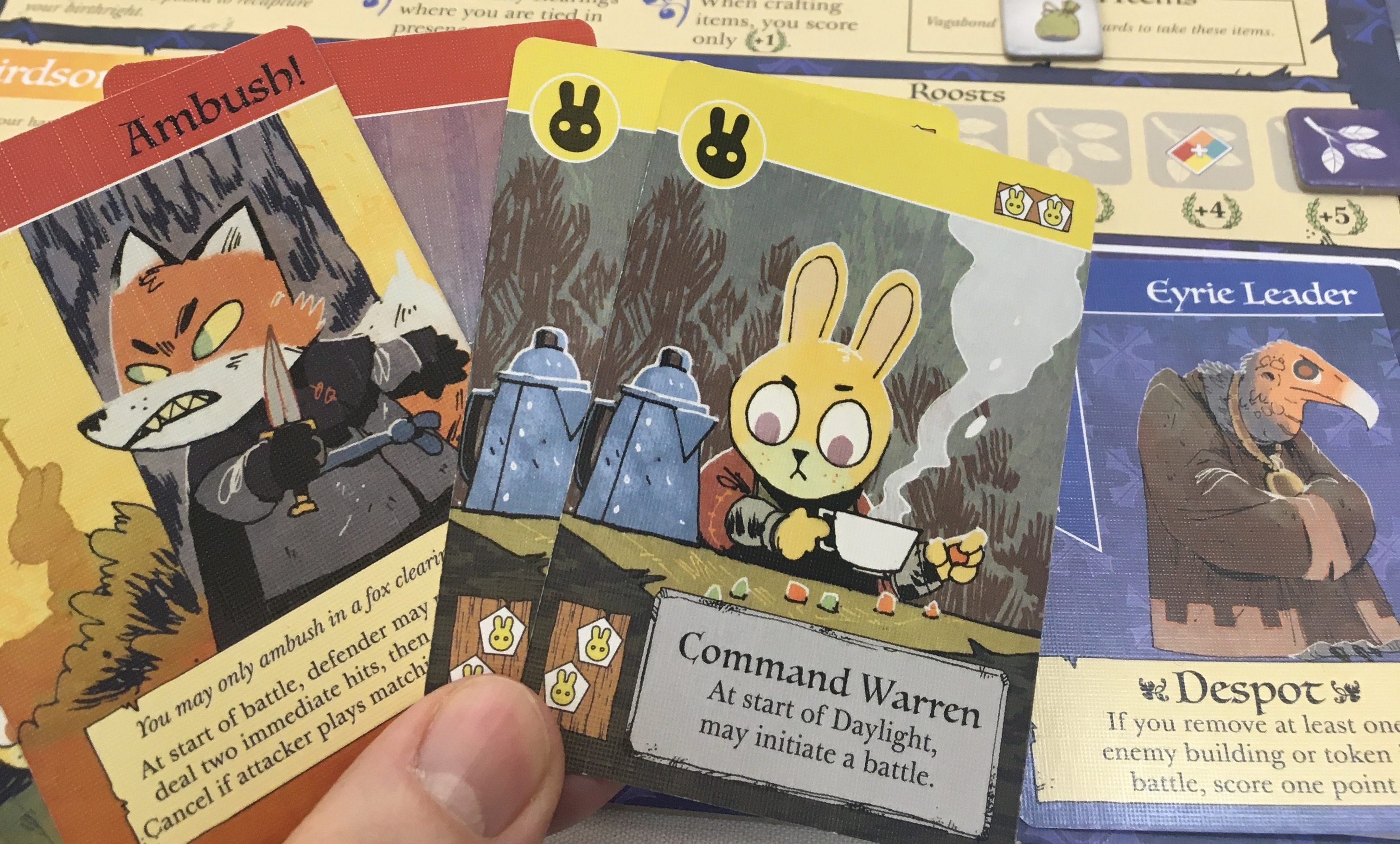 Photograph of several cards from the board game Root, featuring cartoon art of foxes and bunnies and birdies dressed for war.