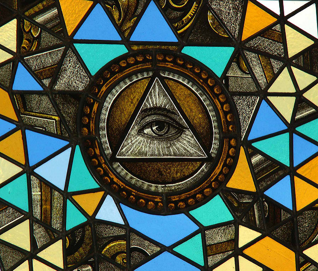 A photograph of a stained-glass window bearing an eye-in-the-pyramid symbol.