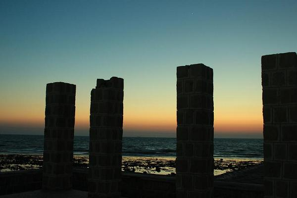 Just after sunset on a beach. Several uncertain rectangular shapes loom in the near distance.