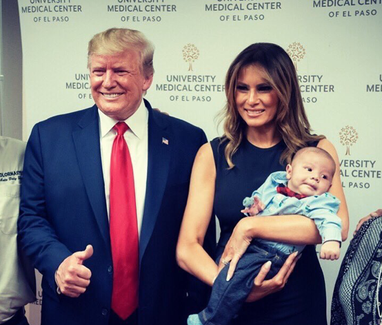 Photograph of Donald and Melania Trump, both grinning at the camera. Melania is cradling a baby whose parents died before its eyes in the El Paso mass shooting. Donald is making a thumbs-up gesture.
